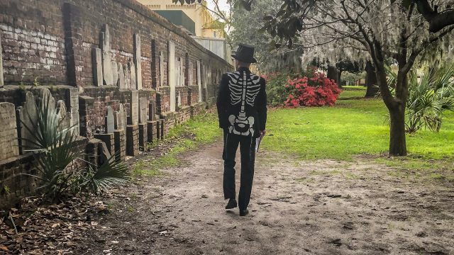 Mr Bones walks along the wall of orphan tombstones