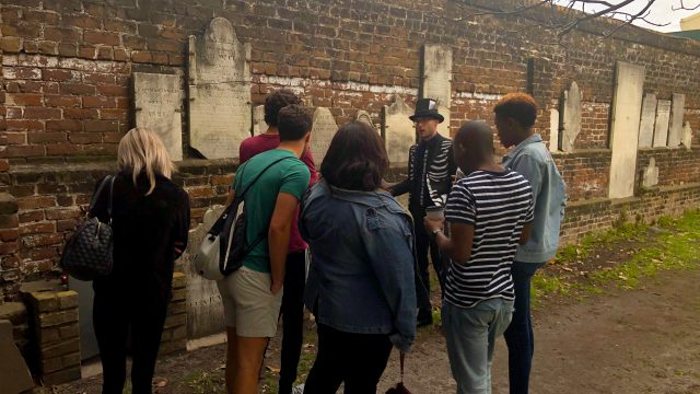 Group gathers around the Muir Stone on an Ole Bones Tour